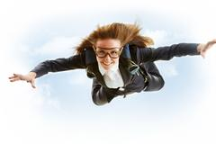 conceptual image of young female flying with parachute on her back - stock photo