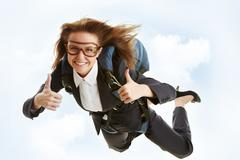 Conceptual image of young female flying with parachute and showing thumbs up Stock Photos