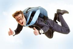 Portrait of happy man flying with parachute and showing thumbs up Stock Photos
