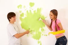 affectionate couple looking at each other while painting walls in new house - stock photo
