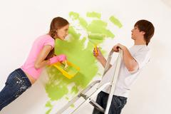 Industrious couple looking at each other while painting walls in new house Stock Photos