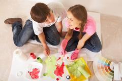 Above angle of young couple mixing paints while sitting on floor in new flat Stock Photos