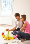 Photo of young couple speaking while mixing paints during flat improvement Stock Photos