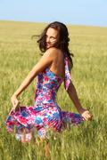 Photo of pretty brunette in colorful dress in wheat field looking at camera Stock Photos