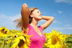 photo of pretty girl among sunflowers having nice time on sunny day - stock photo