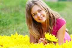photo of pretty girl with sunflower looking at camera on sunny day - stock photo