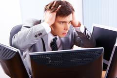 portrait of frustrated employer surrounded by computers with his hands on head - stock photo