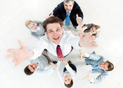 Image of businessman stretching his hands to the camera surrounding by his colle Stock Photos