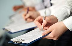 row of hands of business people holding documents and pens - stock photo