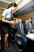 image of pretty stewardess giving glass to businessman in airplane - stock photo