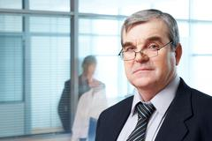 portrait of mature boss in eyeglasses looking at camera - stock photo