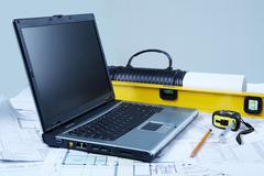 Photo of opened laptop with engineering objects and documents at workplace Stock Photos
