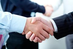 row of businesspeople handshaking with each other - stock photo