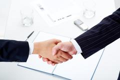 woman and man shaking hands over paper, pen, phone, glasses - stock photo