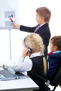 Photo of cute children looking at whiteboard while smart lad presenting project Stock Photos