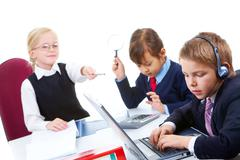photo of serious businesschild with headset typing on background of smart girls - stock photo