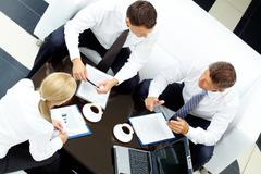 photo of successful partners discussing business plan at meeting - stock photo
