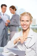 confident businesswoman looking at camera at background of communicating people - stock photo