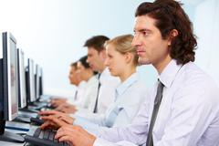 photo of serious businesspeople typing and looking at monitors in line - stock photo