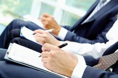 close-up of business people hands with document writing at lecture - stock photo