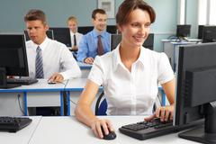 businesspeople sitting at tables and looking at their monitors with smiling woma - stock photo