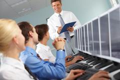 Photo of young businesspeople looking at confident teacher during computer studi Stock Photos