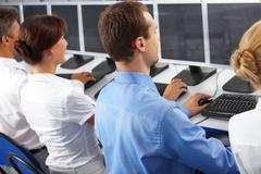 back view of businesspeople typing and looking at monitors in line - stock photo