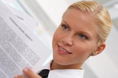 portrait of pretty businesswoman reading document - stock photo