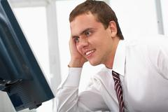 Image of young successful employer looking at computer monitor on workplace Stock Photos