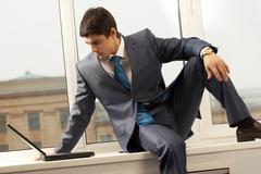 Photo of smart businessman sitting on window-sill with laptop near by and lookin Stock Photos