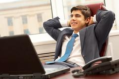 Portrait of smart businessman thinking about something with smile in office Stock Photos