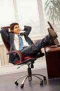 portrait of handsome employee having rest in arm-chair in office - stock photo