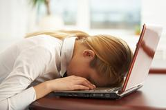 image of very tired businesswoman or student with her face on keyboard of laptop - stock photo