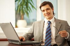 portrait of confident businessman with eyeglasses looking at camera and smiling - stock photo