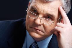 photo of senior employer thinking about something on black background - stock photo