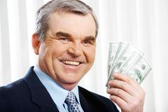 Photo of happy senior businessman showing dollar banknotes Stock Photos