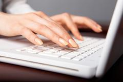 human hands over laptop keypad during typing - stock photo