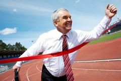 Photo of happy mature businessman crossing finish line during race Stock Photos
