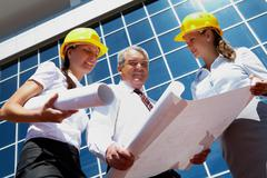 Photo of business partners in helmets on background of modern office building Stock Photos