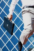 Close-up of businessman with briefcase running Stock Photos
