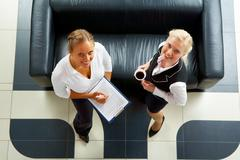 above angle of two friendly employees standing by sofa and looking at camera - stock photo