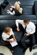 above angle of man and woman sitting on sofa and planning work while secretary t - stock photo