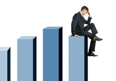 image of pensive businessman sitting on chart columns - stock photo
