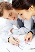 successful businessman and his pretty colleague discussing papers - stock photo