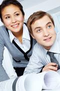 successful colleagues looking aside with smiles during work - stock photo