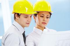 Portrait of two architects in helmets looking document at meeting Stock Photos