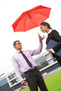 Portrait of handsome man holding red umbrella above female head Stock Photos