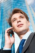 View from below of confident businessman speaking on the phone outdoors Stock Photos