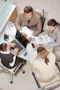 above view of executive business group sitting at desk in office and working - stock photo
