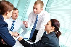 Image of smart employees looking at confident businessman while he explaining so Stock Photos